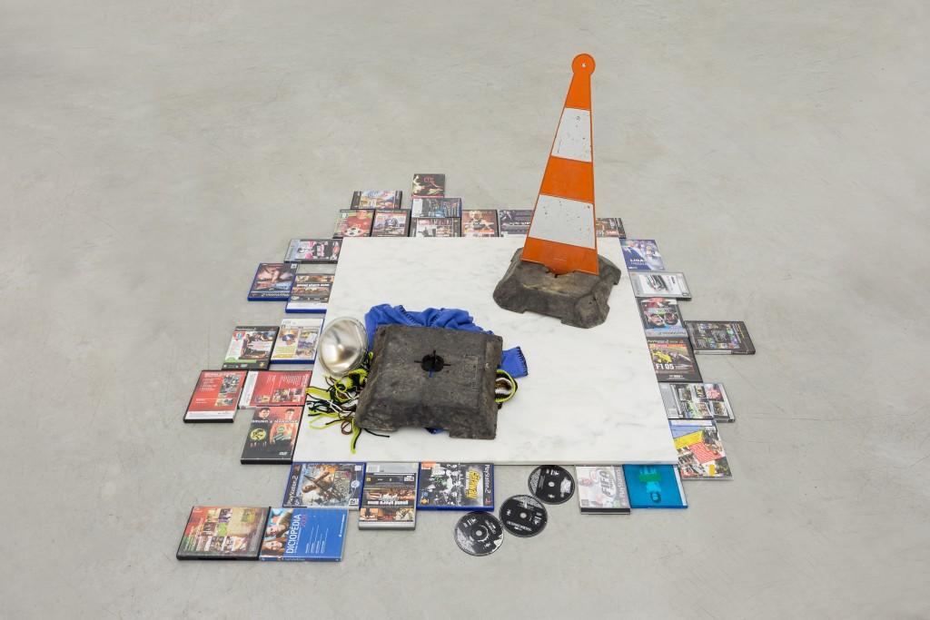 Mauro Cerqueira DVDPS2/3, 2014 Marbre, dvd, jeux de playstation, pull, lampe, cône signalétique 177 X 165 X 76 cm Courtoisie Galeria Múrias Centeno