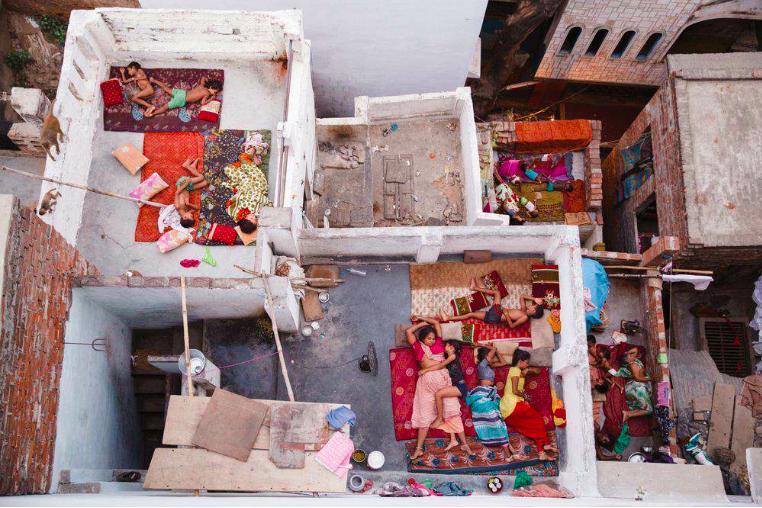 """Deuxième place, catégorie """"gens"""" © Yasmin Il était 5h30 du matin et je venais d'arriver à Varanasi (Bénarès), en Inde, après un voyage en train couchettes. Je suis arrivée dans ma maison d'hôtes et j'ai instinctivement gravi les escaliers des sept étages pour voir le lever du soleil sur le Gange. Lorsque j'ai regardé les toits, j'ai été surprise par ces familles qui dormaient là pour survivre à la chaleur étouffante de Varanasi. Au passage, saurez-vous repérer le curry sur la photo ?"""