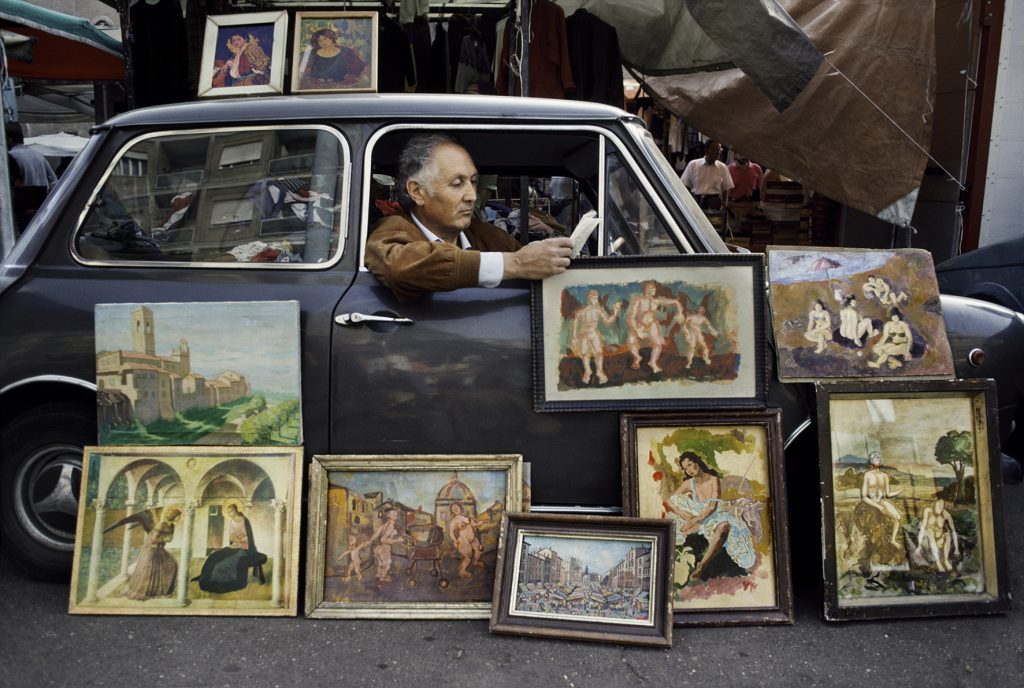 00472_20, Rome, Italy, 1984, ITALY-10041NF. A man displays paintings while he reads in his car. © Steve McCurry