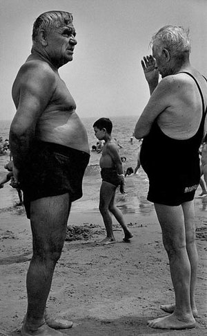 Two men stand on the beach talking while a boy walks by making a similar gesture, Coney Island, New York, 1950, Courtesy Galerie Thierry Bigaignon.